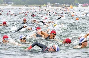 体力の限界に挑む鉄人レースで、力泳する選手たち=日、猪苗代湖天神浜
